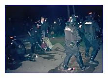 Náhodně vybranou demonstrantku táhnou strážníci zakordon